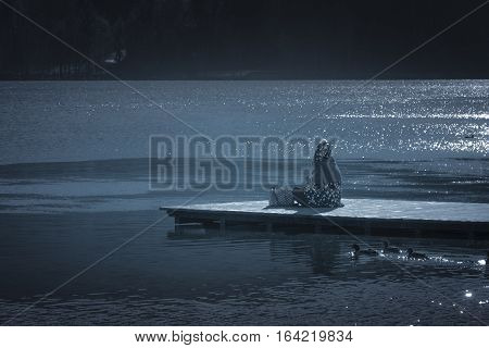 Girl on wooden pier on lake Bled - Girl with hood sitting on a wooden pier on the lake Bled in Slovenia in a sunny day of winter