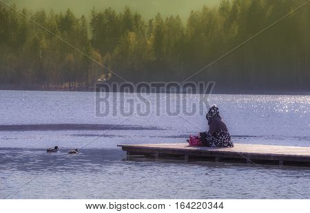 Young woman sitting on lake Bleds pier - Young Slovenian woman sitting on a wooden pier in a December morning day at lake Bled in Slovenia