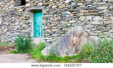 An old stone barn with a turquoise door in the valley of Martindale in Cumbria in the English Lake District.