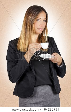 Business woman drinking coffee in cup. Work pause. A standing woman having a coffee during her coffee break. The beautiful young woman is drinking holding a small white cup of coffee. Gradient brown background with grain