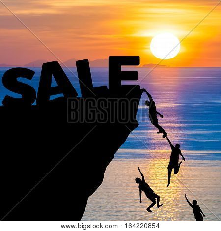 Silhouette of people climbs into cliff to reach the word SALE with sunrise (Shopping concept)