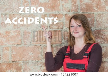 Young woman dressed in red overall is standing in front of an old brick wall. Woman is looking at the camera and is pointing the finger at the sign Zero Accidentsl.