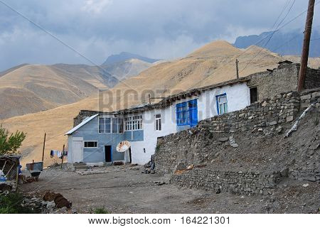 Xinaliq, Azerbaijan - August 23, 2014. Residential house in Xinaliq village, with linen put out to dry, satellite antenna and mountains in the background.