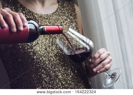 Horizontal close up of Caucasian retro woman in gold sequin vintage dress pouring red wine into a tall glass in a bar