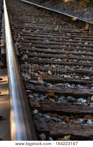A limited selective focus of a view of the railroad rails and railroad ties on a train track