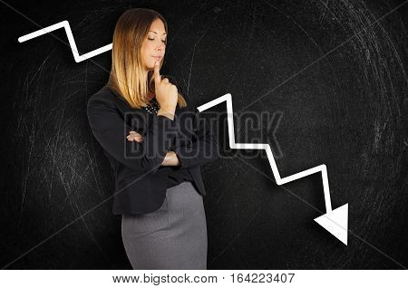 Crisis. Chart loss. Business woman worried. A beautiful business woman is worried about corporate losses. Brushed black background with scratches. Crisis. Chart loss. Business woman worried.