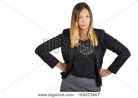Woman angry. Aggressive attitude. On white background. A beautiful business woman has her fists on her hips and a defiant attitude. White background. Concept of female anger and aggression.