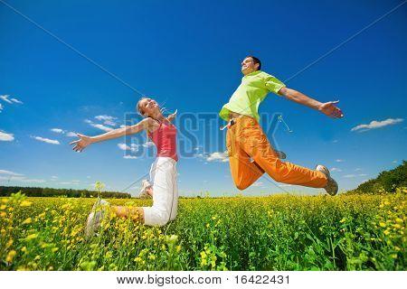 Pessoas felizes está saltando no campo
