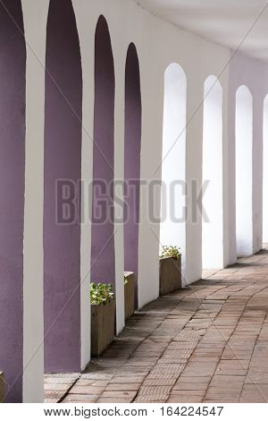 Curved archway in clean purple and white coloured arches