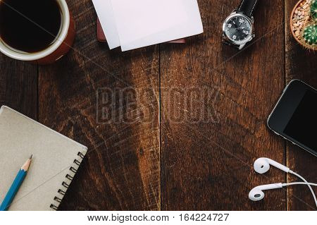 Top view accessories office desk the mobile phone tag pencil note paper coffee cactus earphones on wooden office desk background. poster