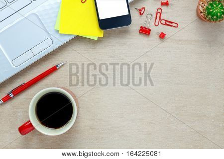 Top view notebook pencil black coffee cactus note paper smartphone Laptop stationary on office desk background.
