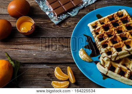Wooden table with Viennese waffles, tangerines, chocolate