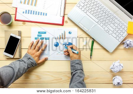 Top view business person discussing charts and graphs with laptop coffee smartphone pen notebook on office desk.