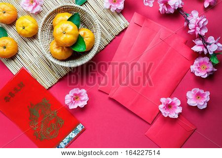 Top view accessories Chinese new year festival decorations.orange leaf wood basket red packet plum blossom on red background.Foreign language means be rich and Happy.