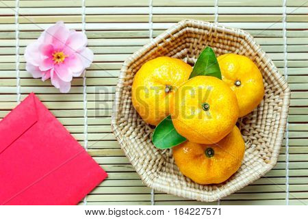 Top view accessories Chinese new year festival decorations.orange leaf wood basket red packet plum blossom on bamboo background.
