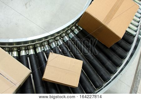Boxes on conveyor belt in logistics distribution warehouse.
