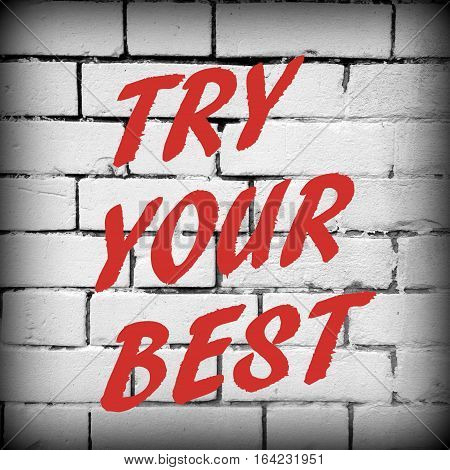 The words Try Your Best in red text on a white brick wall as a reminder to give everything your best effort to achieve success