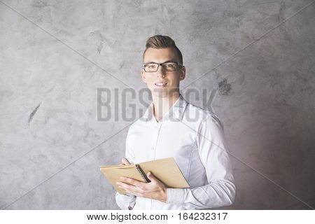 Attractive white businessman with spiral notepad in hand. Paper work concept