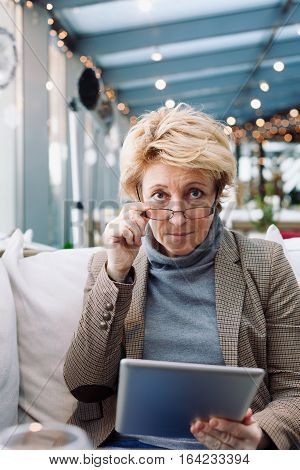 Mid age woman with tablet sitting at indoor cafe looking in camera