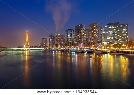 Panoramic Paris cityscape with Eiffel tower, quay de Grenelle and Andre Citroen and its reflection in the river Seine at night, as seen from bridge Pont Mirabeau, France