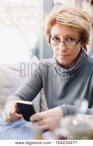 Mid age woman with cell phone sitting at indoor cafe looking in camera