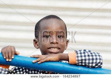This smiling child is backed by an iron bar.