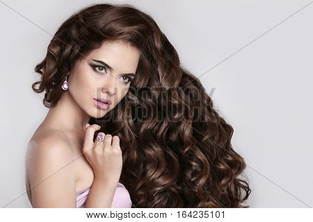 Long Curly Hair. Beautiful Brunette Girl Portrait With Long Shiny Wavy Hairstyle. Fashion Elegant Mo