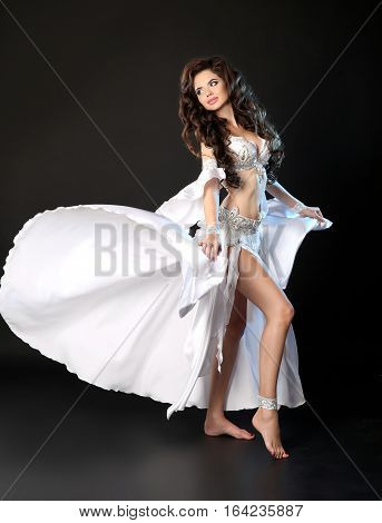 Bellydance. Beautiful Arabic Sexy Belly Dancer In Blowing White Dress Dancing Isolated On Black Stud