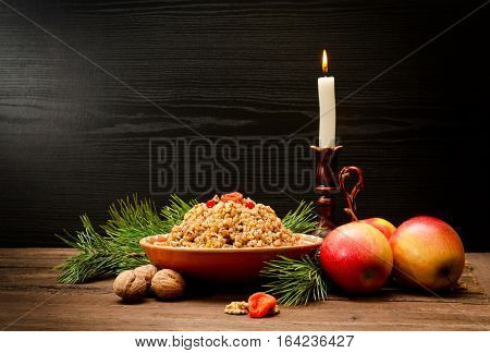 Traditional Christmas treat of the Slavs on Christmas eve kutia. Fir branch apples candle on wooden background. Place for text