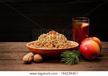 Plate with traditional Christmas treat Slavs on Christmas Eve. Compote spruce branch apples on a black background. Space for text