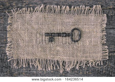Old metal key lying on a canvas a piece of fabric