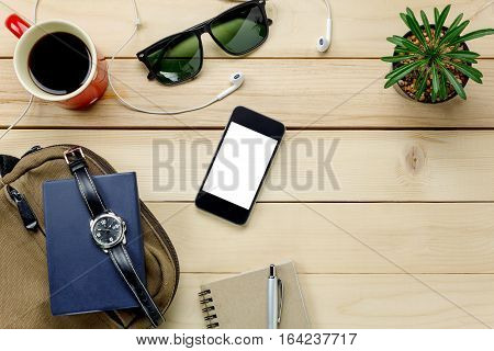 Top view accessories travel with mobile phone sunglasses bag watch notepaper earphones pen cactus coffee on table wooden with copy space.Travel concept.
