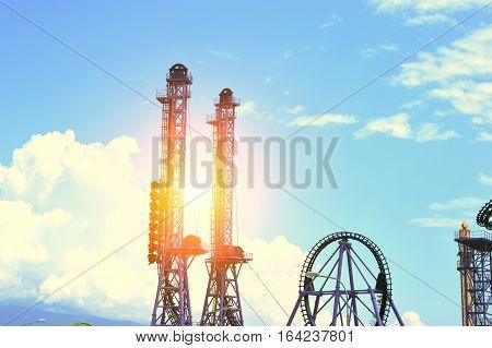 Amusement park. Silhouette of roller coaster against sunlight