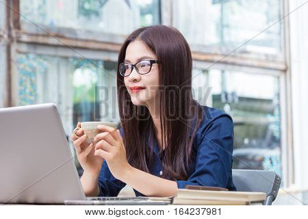 young asian woman holding cup of coffee and taking a break from woking on her computer