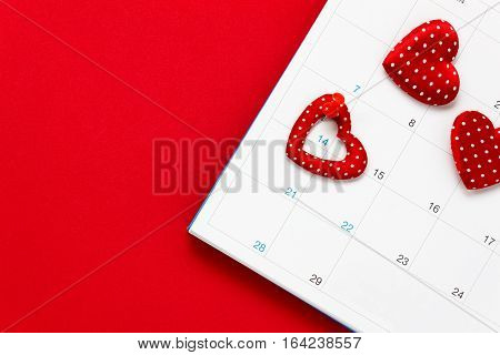 Top view valentines day background.the red pin mark February 14 at calendar on red background and heart shape with copy space.