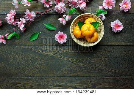 Top view orange leaf wood basket plum blossom on table wooden background with copy space.