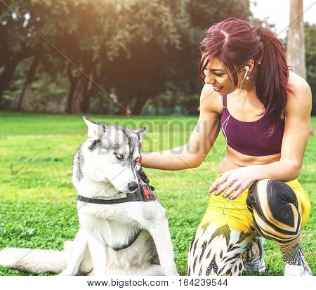 Beautiful young sportswoman taking a break from a workout to cuddle her dog Husky