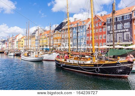 13, July, 2016, Copenhagen, Nyhavn. Colourful houses reflect in the water. Fishing boats is in the harbor and tourists from all over the world stroll along the quay. The oldest house dating back to 1681.