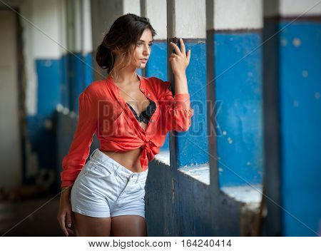 Beautiful girl with red shirt and white shorts posing in old hall with columns blue painted. Attractive long hair brunette, side view against ancient pillars. Dark hair young woman with gorgeous eyes