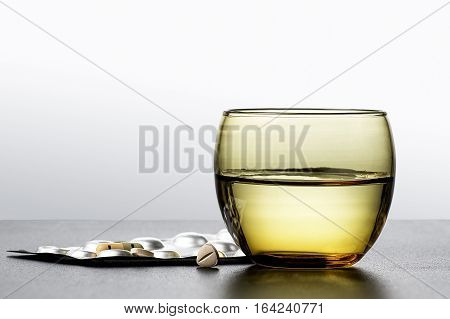 Medicinal pills and capsules whith glass of water