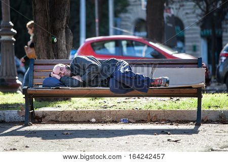 ROME, ITALY - January 10, 2016: Homeless man sleeping on the bench. A poor homeless man is sleeping on the bench in the historic center of Rome, Italy. Daytime scene