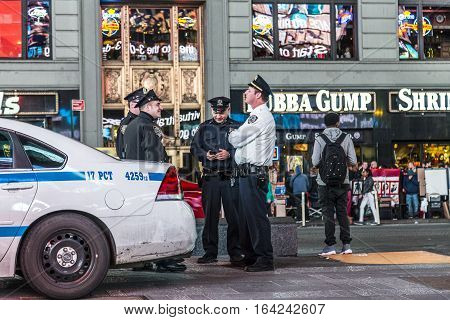 NEW YORK USA - OCT 25 2015: police pays attention at times square by night. Times Square is under 24 hour observation by police to ensure safety for the people.