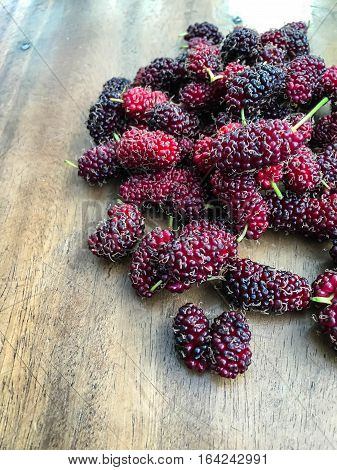 ripe mulberries on a table wood .