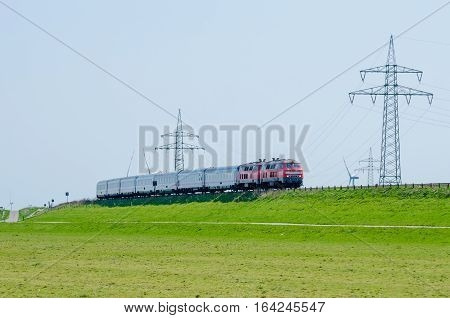 German train driving on Hindenburg Dam towards the island Sylt with green grass and electricity poles, Germany.