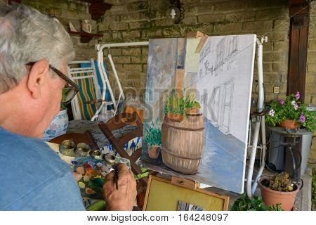 Senior Man painting a picture with oil colors choosing the color on the palette