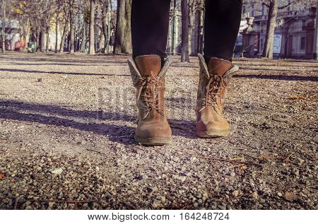 girl walking on a path in a park feet in shoes closeup