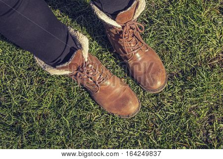girl in shoes standing on the grass walk in the park.
