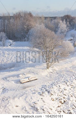 Two snowy beches covered with snow in a park at winter