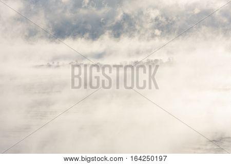 Island far in distance in a foggy sea