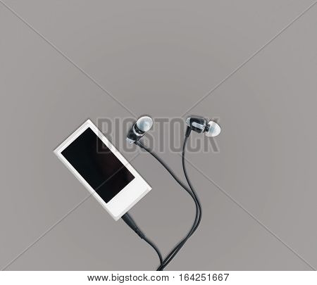 Small white portable MP3 digital music player with earbuds against a grey background